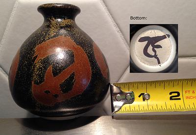 Small Japanese looking stoneware art studio pot with narrow neck and bulbous shape with red kanji characters on the black ground with brown speckle decoration and a black kanji pottery marking