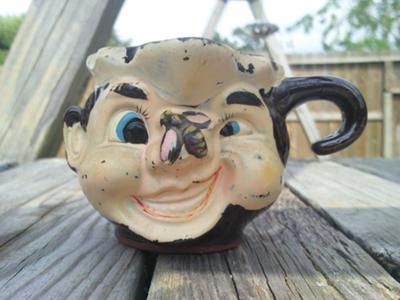 Character mug with a gold N inside a gold circle